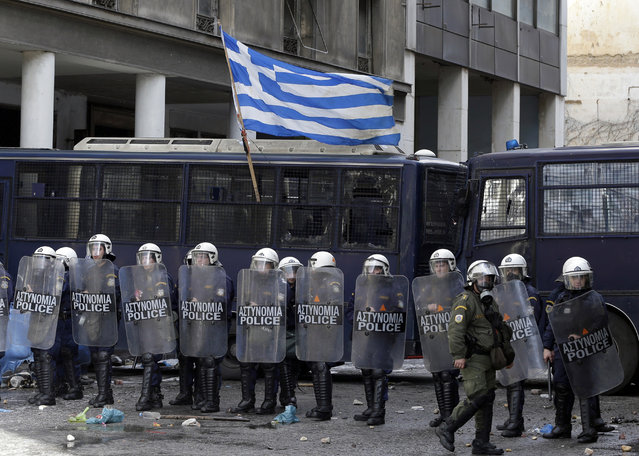 A Greek flag waves on a police vehicle as riot policemen guard the Agriculture Ministry during clashes with farmers, in Athens, Wednesday, March 8, 2017. More than 1,000 farmers from the Greek island of Crete protesting against bailout-related income cuts clashed with riot police. (Photo by Thanassis Stavrakis/AP Photo)