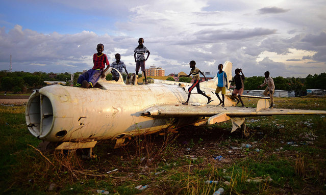 Children play on a destroyed fighter plane in Juba on April 21, 2016. Fragile hopes for an end to South Sudan's civil war are being tested by the rebel leader's failure to return to the capital to form a unity government. International pressure is growing after Riek Machar, a former rebel leader turned deputy president who was fired, became a rebel leader again and has now fought his way back to the vice presidency, failed to appear in Juba as expected on April 18 or 19. (Photo by Carl de Souza/AFP Photo)