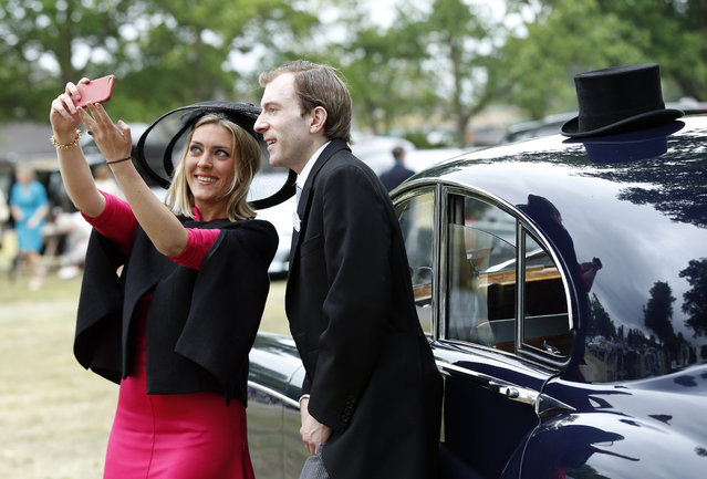 William and Milly Beddall pose for a selfie as they arrive for the second day of  Royal Ascot horse racing meet at Ascot, England, Wednesday, June 17, 2015. Royal Ascot is the annual five day horse race meeting that Britain's Queen Elizabeth II attends every day of the event.(AP Photo/Alastair Grant)