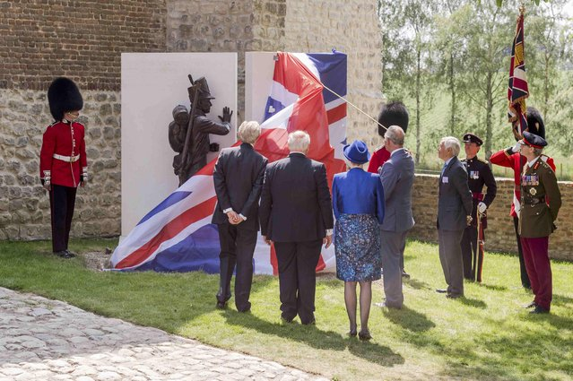 Britain's Prince Charles (4thL) holds a cord as he unveils a monument during a ceremony for the opening of the Hougoumont farm as part of the bicentennial celebrations for the Battle of Waterloo, near Waterloo, Belgium June 17, 2015. The commemorations for the 200th anniversary of the Battle of Waterloo will take place in Belgium on June 19 and 20. REUTERS/Geert Vanden Wijngaert/Pool