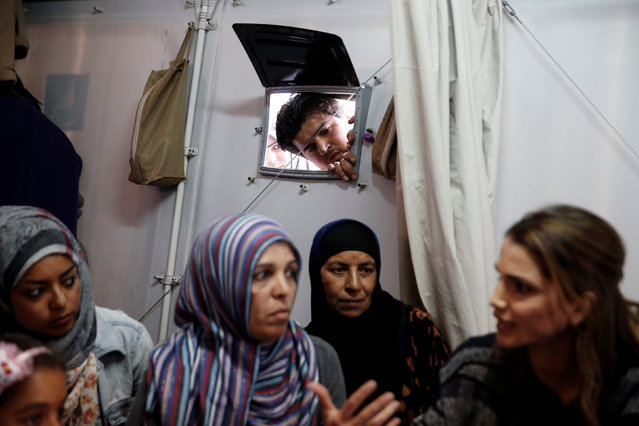 A refugee peeks through a window as Queen Rania of Jordan (R) meets with Syrian refugee women during her visit at the Kara Tepe refugee camp on the island of Lesbos, Greece, April 25, 2016. (Photo by Alexandros Avramidis/Reuters)