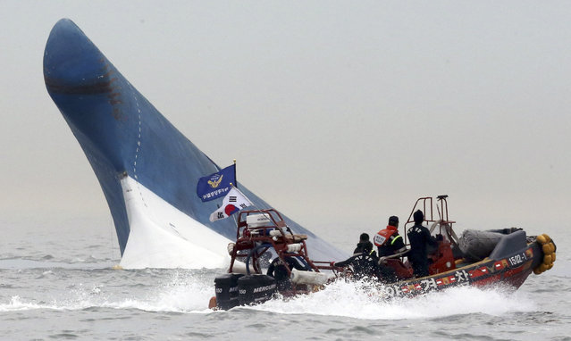 South Korean coast guard officers try to rescue passengers from a ferry sinking in the water off the southern coast near Jindo, south of Seoul, South Korea, Wednesday, April 16, 2014. The ferry carrying 459 people, mostly high school students on an overnight trip to a tourist island, sank off South Korea's southern coast on Wednesday, leaving nearly 300 people missing despite a frantic, hours-long rescue by dozens of ships and helicopters. At least four people were confirmed dead and 55 injured. (Photo by AP Photo/Yonhap)