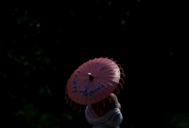 A woman holds an umbrella in Lafayette Park near the White House during a heat wave in Washington, U.S., July 20, 2019. (Photo by Eric Thayer/Reuters)