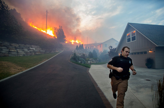 In this Sunday, June 28, 2015 photo provided by The Wenatchee World, a Chelan County Sheriff's deputy races to check that all residents have left their home as flames approach houses at Quail Hollow Lane in Wenatchee, Wash. A wildfire fueled by high temperatures and strong winds roared into the central Washington neighborhood, destroying properties and forcing residents of several hundred homes to flee, authorities said Monday. (Photo by Don Seabrook/The Wenatchee World via AP Photo)