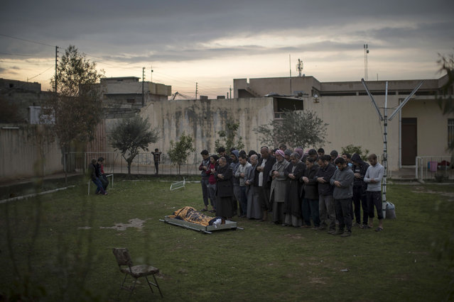 Relatives and friends pray next to the body of Suheyil Najn Abdullah after he was killed by a sniper trying to flee fighting between Iraqi security forces and Islamic State on the western side of Mosul, Iraq, Thursday, March 23, 2017. (Photo by Felipe Dana/AP Photo)