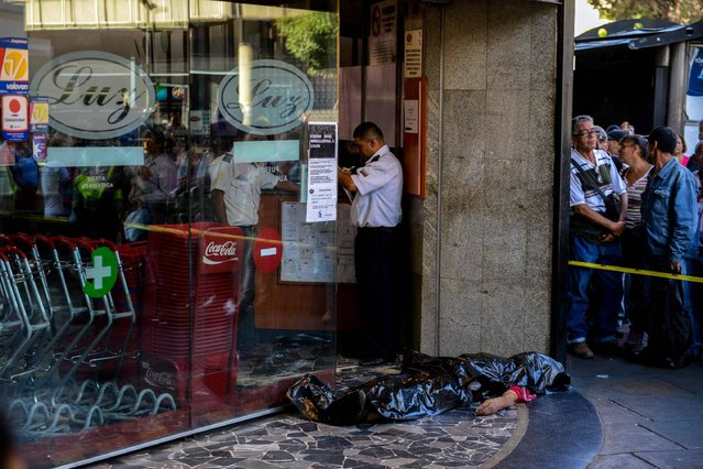 The body of a man lies outside a supermarket, where he died of a heart attack after waiting in a long line to buy food, in Caracas on March 30, 2017. (Photo by Federico Parra/AFP Photo)