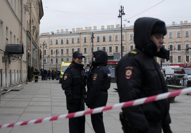Russian police officers stand guard in a street after a explosion in St. Petersburg's subway, Russia, Monday, April 3, 2017. (Photo by Evgenii Kurskov/AP Photo)