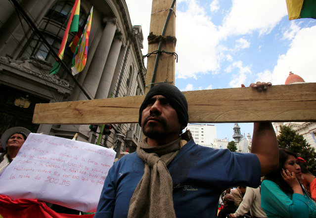 A demonstrator with physical disabilities, who is carrying a cross, participates in a rally protest calling on the government to increase their monthly disability subsidy, in La Paz, Bolivia, May 5, 2016. (Photo by David Mercado/Reuters)