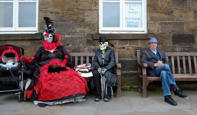 Two goth women sit on a bench during the Goth weekend on April 26, 2014 in Whitby, England. The Whitby Goth weekend began in 1994 and happens twice each year. Thousands of extravagantly dressed people who follow Steampunk, Cybergoth, Romanticism or Victoriana visit the town to take part in the celebration of Goth culture. (Photo by Ian Forsyth/Getty Images)