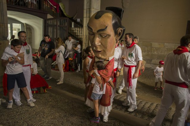 A Cabezudo figure hugs a child after a procession in Pamplona, Spain, Thursday, July 9, 2015. Revelers from around the world arrive in Pamplona every year to take part in some of the eight days of the running of the bulls. (Photo by Andres Kudacki/AP Photo)