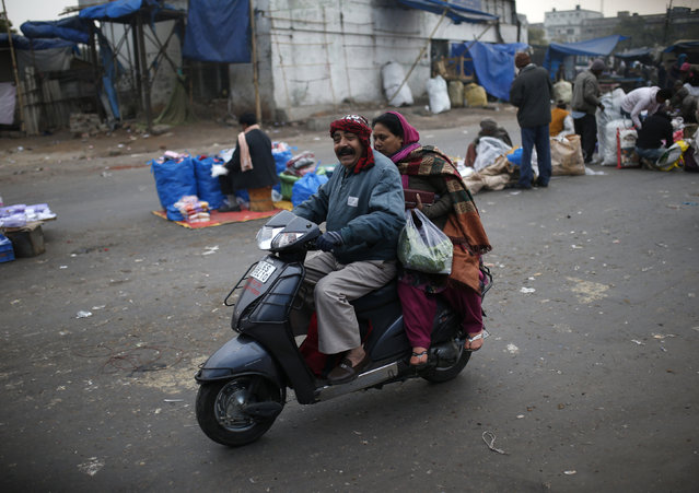 A couple ride a scooter in a market place on a cold winter morning in the old quarters of Delhi December 31, 2014. (Photo by Ahmad Masood/Reuters)