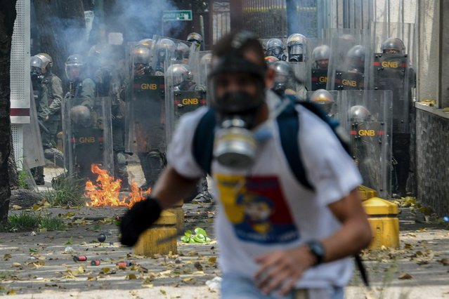 A demonstrator runs during a protest against Venezuelan President Nicolas Maduro, in Caracas on April 19, 2017. (Photo by Federico Parra/AFP Photo)