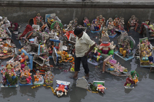 An Indian man forages for reusable items amid idols of Hindu elephant headed god Ganesha and offerings, a day after the immersion of idols, in Ahmadabad, India, Friday, September 13, 2019. Every year millions of devout Hindus immerse Ganesha idols into oceans and rivers during the ten-day long Ganesh Chaturthi festival that celebrates the birth of the Hindu god. (Photo by Ajit Solanki/AP Photo)
