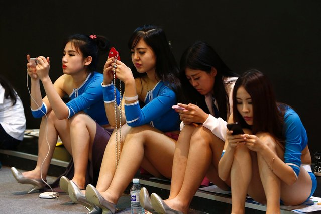 Promotional models use their smartphones during their break at the Global Mobile Internet Conference in Beijing May 6, 2014. Mobile Internet industry executives, developers and investors from more than 30 countries took part in the Global Mobile Internet Conference in Beijing, the organiser said. (Photo by Kim Kyung-Hoon/Reuters)