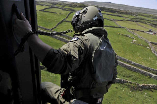 Corporal Patrick Mahon directs instructions for landing as the Irish Air Corps deliver maintenance and repair supplies to Dun Aonghasa, a pre-historic stone fort dated from 1100BC on the remote Aran Islands in Galway, Ireland May 13, 2016. (Photo by Clodagh Kilcoyne/Reuters)