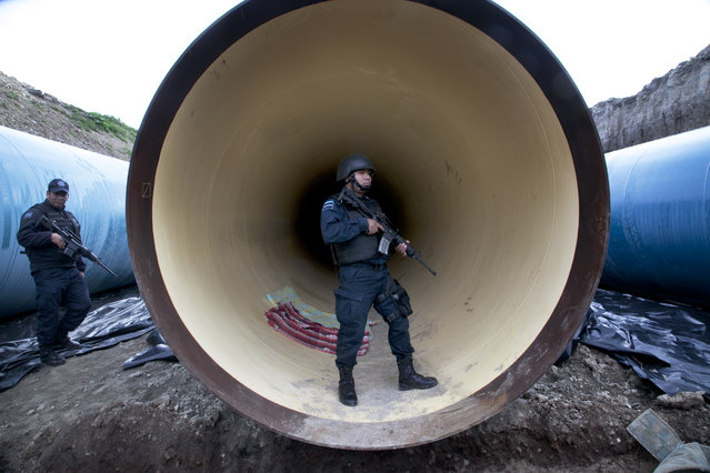"Federal police guard a drainage pipe outside of the Altiplano maximum security prison in Almoloya, west of Mexico City, Sunday, July 12, 2015. Mexico's most powerful drug lord, Joaquin ""El Chapo"" Guzman, escaped from a maximum security prison through a tunnel that opened into the shower area of his cell, the country's top security official announced. (Photo by Marco Ugarte/AP Photo)"