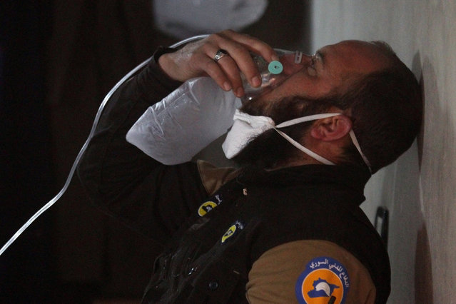 A civil defence member breathes through an oxygen mask, after what rescue workers described as a suspected gas attack in the town of Khan Sheikhoun in rebel-held Idlib, Syria April 4, 2017. (Photo by Ammar Abdullah/Reuters)