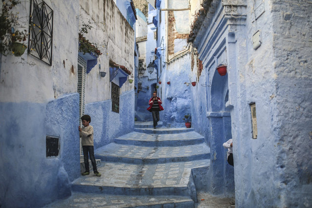 A boy plays outside his house while a man walks down an alleyway in the Medina of Chefchaouen, a picturesque town well-known for its blue painted houses and alleyways, in northern Morocco, Saturday, April 29, 2017. (Photo by Mosa'ab Elshamy/AP Photo)