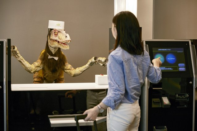 """An undated handout image provided by amusement park operator Huis Ten Bosch Co., Ltd. shows a woman standing before a receptionist dinosaur robot at the """"Henn na Hotel"""" (or Weird Hotel) in Sasebo, Nagasaki prefecture, southwestern Japan, 16 July 2015. Almost entirely run by robots, the new hotel will open to the public on 17 July. (Photo by Huis Ten Bosch/EPA)"""