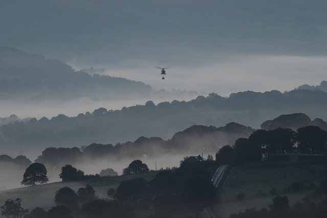 Mist is seen in the valleys before sunrise as a Chinook helicopter prepares to drop sandbags onto the dam wall at Toddbrook reservoir following a severe structural failure after heavy rain, on August 02, 2019 in Whaley Bridge, England. The town's 6,500 people were forced to leave their homes after yesterday's partial collapse of the dam at Toddbrook Reservoir, in Derbyshire. Engineers have been pumping water from the reservoir overnight to reduce the water level. (Photo by Leon Neal/Getty Images)