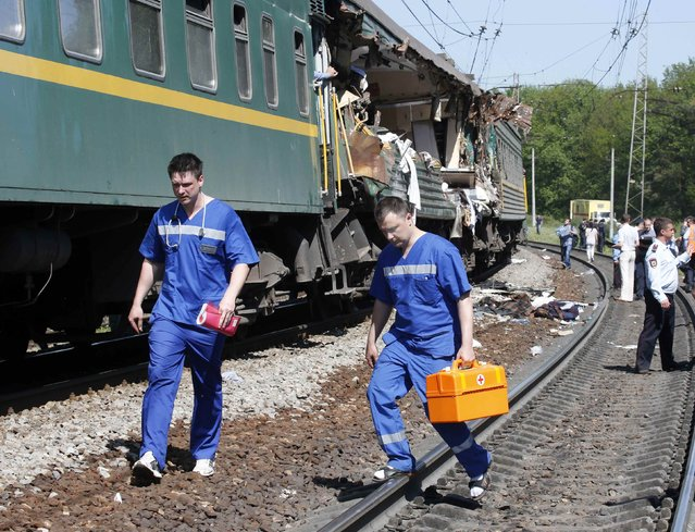 Medical personnel walk near a passenger train damaged in a collision with a freight train in Moscow region May 20, 2014. A passenger train on its way to Moldova collided with a freight train near Moscow on Tuesday, killing at least four people and injuring 15, a spokeswoman for Russia's Emergencies Ministry said. The reason for the collision, near the town of Naro-Fominsk 55 km (34 miles) southwest of Moscow, was not immediately clear. (Photo by Grigory Dukor/Reuters)
