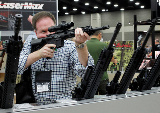 James Bell from Nashville, TN, look over rifle scopes from Burris Riflescope at the National Rifle Association's annual meetings and exhibits show in Louisville, Kentucky, May 21, 2016. (Photo by John Sommers II/Reuters)
