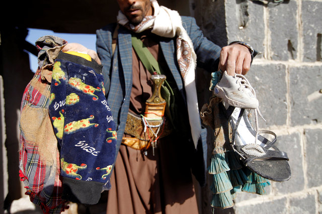 A man show clothes of victims at the site of a Saudi-led air strike which struck a house where mourners had gathered for a funeral north of Yemen's capital Sanaa, February 16, 2017. (Photo by Mohamed al-Sayaghi/Reuters)