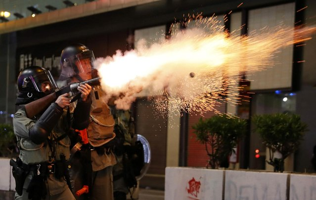 A riot police officer fires a tear gas canister toward anti-government demonstrators during a protest in Hong Kong's tourism district of Tsim Sha Tsui, China on October 27, 2019. (Photo by Ammar Awad/Reuters)