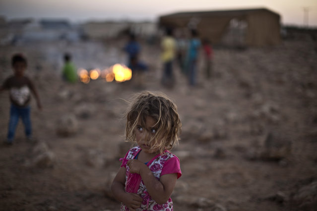 Syrian refugee child Shahd Qadura, 2 1/2, stands by other children burning garbage at an informal tented settlement near the Syrian border on the outskirts of Mafraq, Jordan, Tuesday, July 21, 2015. (Photo by Muhammed Muheisen/AP Photo)