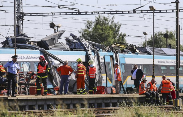 Rescue workers inspect a damaged train carriage at the scene of a crash between high-speed train and a truck at a rail crossing in the town of Studenka, east of Prague, Czech Republic, July 22, 2015. A high-speed passenger train collided with a truck at a railway crossing in the Czech Republic on Wednesday, killing two people and injuring others, the police said. (Photo by Reuters/Stringer)
