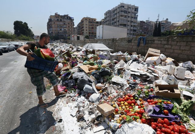 A Lebanese man throws more trash on a pile of garbage covered with white pesticide in the Palestinian refugee camp of Sabra in Beirut, Lebanon, Thursday, July 23, 2015. The Lebanese cabinet has failed to agree on a solution for the country's growing garbage crisis, postponing discussion until next week as trash piles up on the streets. (Photo by Bilal Hussein/AP Photo)