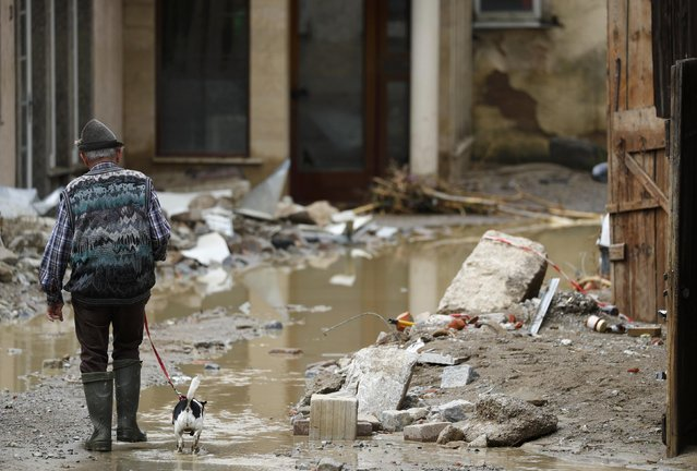An elderly man walks his dog amid debris after the floods in the town of Braunsbach, Germany, May 30, 2016. (Photo by Kai Pfaffenbach/Reuters)