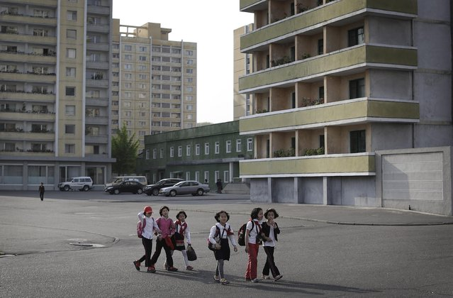 North Korean school children walk past an apartment complex, Tuesday, May 5, 2015 in Pyongyang, North Korea. North Korea is trying to increase the number of residential buildings in the country's capital. (Photo by Wong Maye-E/AP Photo)