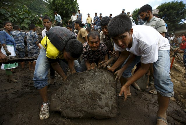 People work to remove a stone as they search for landslide victims at Lumle village in Kaski district July 30, 2015. (Photo by Navesh Chitrakar/Reuters)