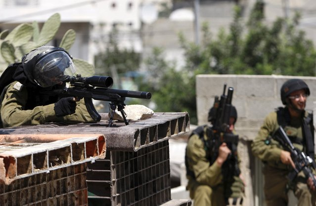 Israeli soldiers take position during clashes with Palestinian protesters in the West Bank city of Hebron July 31, 2015. (Photo by Mussa Qawasma/Reuters)