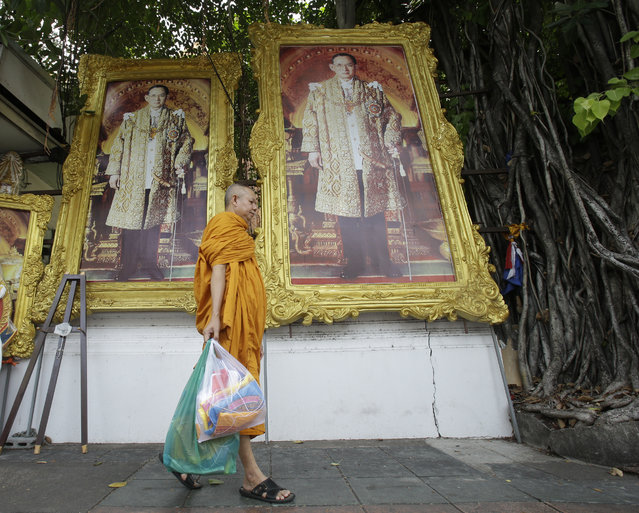 In this Tuesday, June 7, 2016 photo, a Buddhist monk walks past portraits of Thailand's King Bhumibol Adulyadej in Bangkok, Thailand. (Photo by Sakchai Lalit/AP Photo)