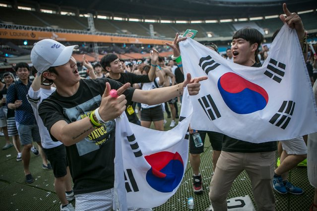 South Korean youths holding Korean flags dance to electronic music during the Ultra Music Festival Korea at Olympic Stadium on June 10, 2016 in Seoul, South Korea. (Photo by Jean Chung/Getty Images)