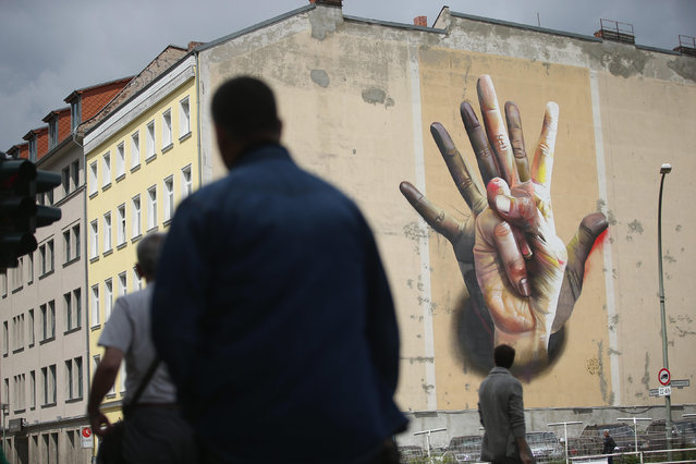 "The giant mural titled ""Under the Hand"" by Maclaim Crew is visible on a building facade in Kreuzberg district on June 26, 2014 in Berlin, Germany. Berlin, with its long tradition of counter-culture, has become a mecca for street art of all dimensions and messages. (Photo by Sean Gallup/Getty Images)"