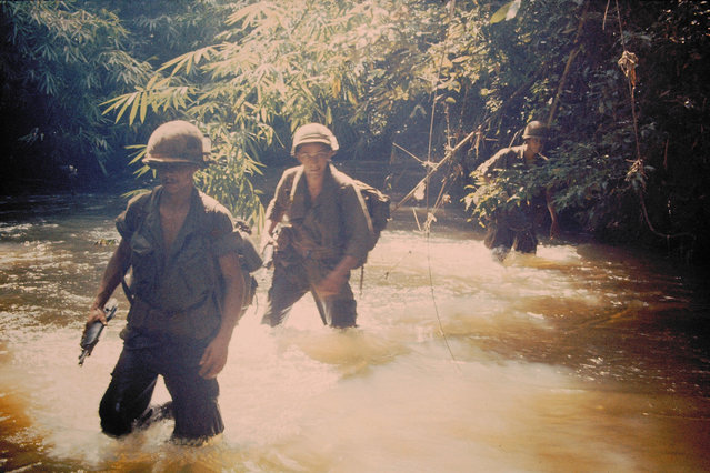 A photo of soldiers crossing a river in Vietnam, from the collection of D. Thornton. (Photo by D. Thornton/The Vietnam Slide Project)