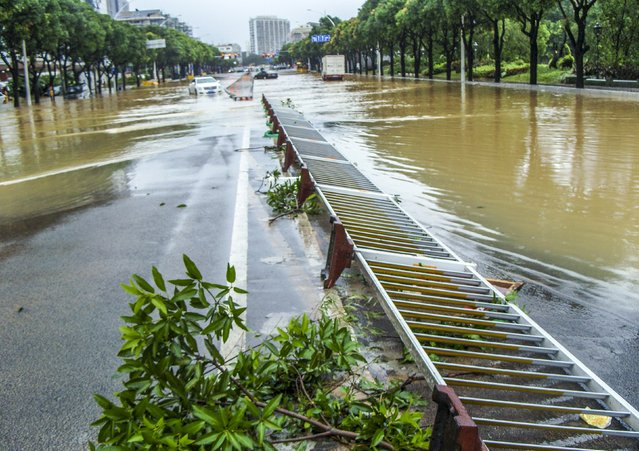 An overturned guardrail is seen on a flooded street after Typhoon Soudelor hit Fuzhou, Fujian province, China, August 9, 2015. Typhoon Soudelor landed on the coast of Putian City in southeast China's Fujian Province late Saturday after lashing Taiwan, bringing strong winds and downpours and causing power outages in the province and neighboring Zhejiang, state media CCTV reported. (Photo by Reuters/Stringer)