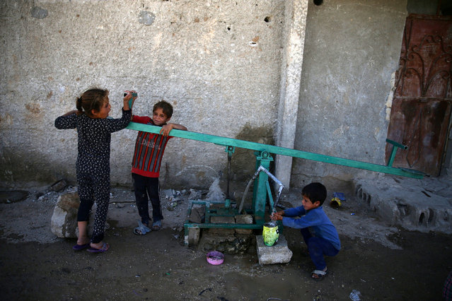 Children pull a lever as they wash up with water, in the rebel held besieged town of Douma, eastern Damascus suburb of Ghouta, Syria, June 23, 2016. (Photo by Bassam Khabieh/Reuters)