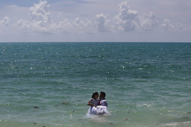A wedding couple poses in the sea during a photo session on Isla Blanca beach in Cancun, Mexico, August 11, 2015. (Photo by Edgard Garrido/Reuters)