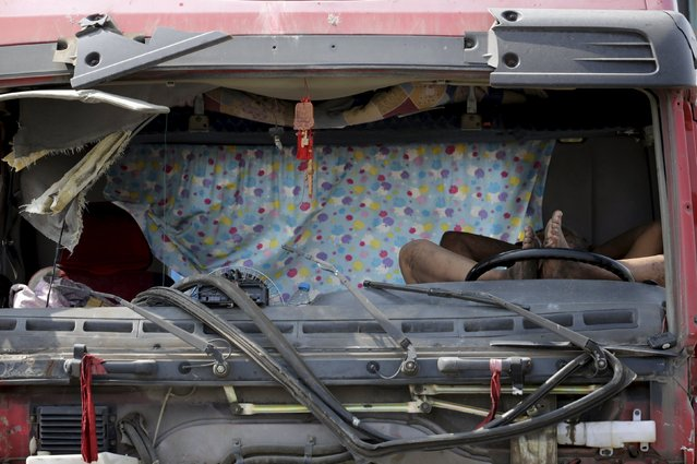 A man sleeps inside a damaged vehicle on a highway near the site of the explosions at the Binhai new district, Tianjin, August 13, 2015. (Photo by Jason Lee/Reuters)