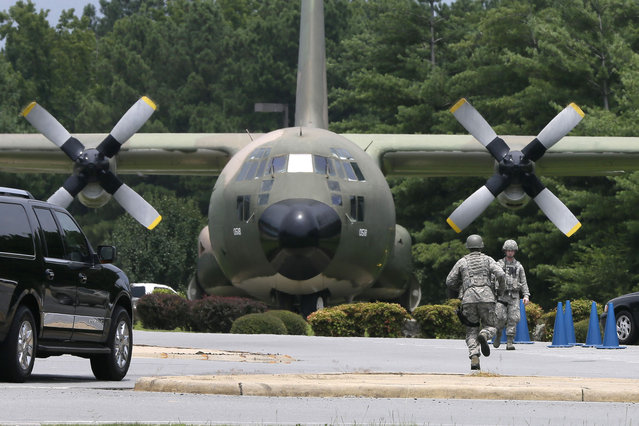 Security personnel run past a C-130 aircraft on static display at the front gate of Little Rock Air Force Base in Jacksonville, Ark., Wednesday, July 23, 2014. The base has been on lockdown since late morning Wednesday. (Photo by Danny Johnston/AP Photo)