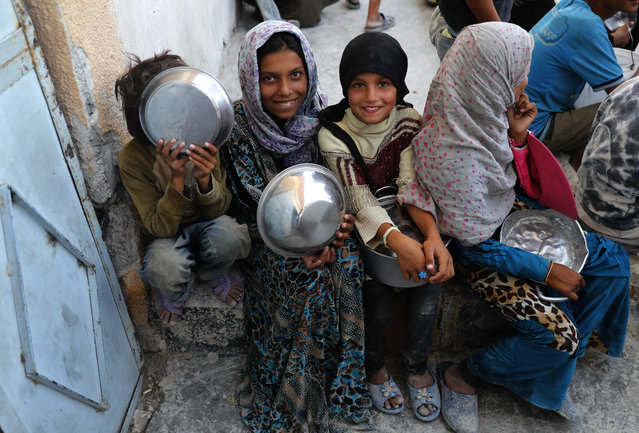 Syrian displaced girls who fled with their families the battle between U.S.-backed Syrian Democratic Forces and the Islamic State militants from Raqqa city, hold their pots as they wait to receive foods at the entrance of the main kitchen of a refugee camp, in Ain Issa town, northeast Syria, Wednesday, July 19, 2017. The U.S. military is supporting local Syrian forces in a campaign to drive IS from Raqqa. (Photo by Hussein Malla/AP Photo)