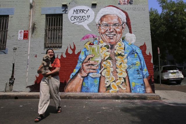 A mural depicting Prime Minister Scott Morrison wearing an unbuttoned Hawaiian shirt, orange lei and Santa Claus hat while holding a cocktail by artist Scott Marsh is seen on a wall in Sydney, Wednesday, December 25, 2019. Morrison was under pressure since taking a much criticized family vacation to Hawaii during the wildfire crisis.(Photo by Steven Saphore/AAP Images via AP Photo)