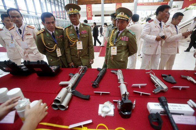 Laotian police officers (in green uniforms) look at Vietnamese-made weapons on display during celebrations to commemorate the 70th anniversary of the establishment of the Vietnam Public Security police force at the National Convention Center in Hanoi August 18, 2015. (Photo by Reuters/Kham)