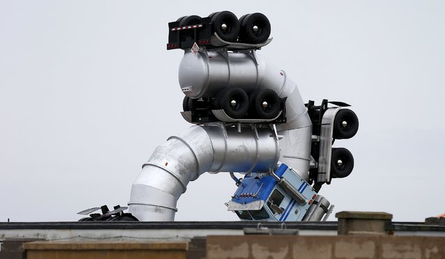 "A seaside ""funfair"" sculpture is seen behind a wall in Weston-super-Mare, southwest England, Britain, August 19, 2015. Local media reports that the creation is a ""dystopian"" theme park created by artist Banksy and will open this weekend. (Photo by Suzanne Plunkett/Reuters)"