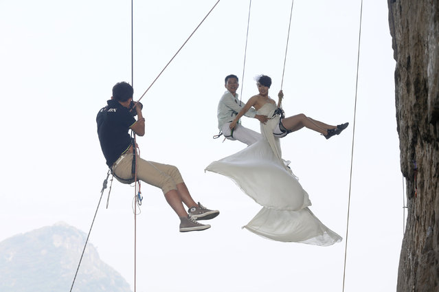 A photographer takes pictures of Fang Jing (R) in a wedding gown next to her husband, surnamed Zhao, as they hang from a cliff during a rock climbing exercise in Liuzhou, Guangxi Zhuang Autonomous Region October 26, 2013. The couple love outdoor sports and they decided to have their wedding photos taken during rock climbing, local media reported. (Photo by Reuters/Stringer)