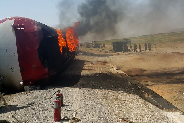 In this photograph taken on May 8, 2016, Afghan bystanders inspect the site of a traffic accident in Ghazni province on the main Kabul-Kandahar Highway. At least 73 people were killed on May 8, 2016, when two passenger buses and an oil tanker burst into flames in a head-on collision in eastern Afghanistan, health officials said, in one of the worst road accidents in the war-battered nation. Bloodied, dazed and badly burned, many of the survivors streamed into Ghazni's main provincial hospital, while many others were rushed in ambulances to health facilities in southern Kandahar city. (Photo by AFP Photo/Stringer)